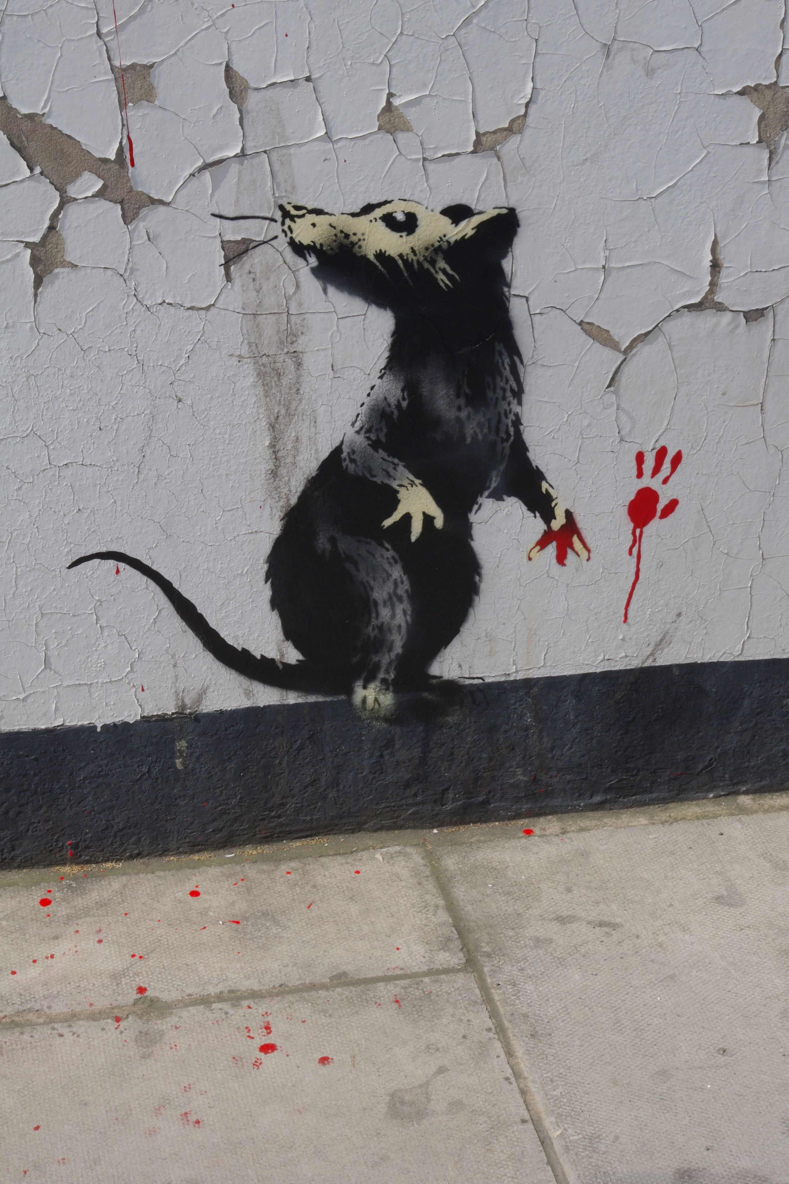A stencil of a rat with red paint on one of its paws