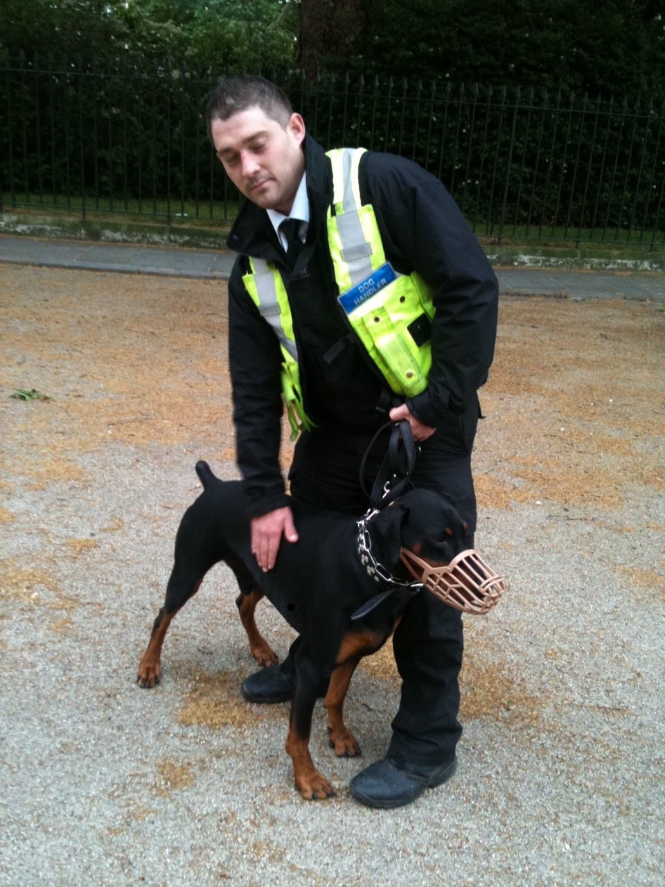 Security guard with muzzled dog