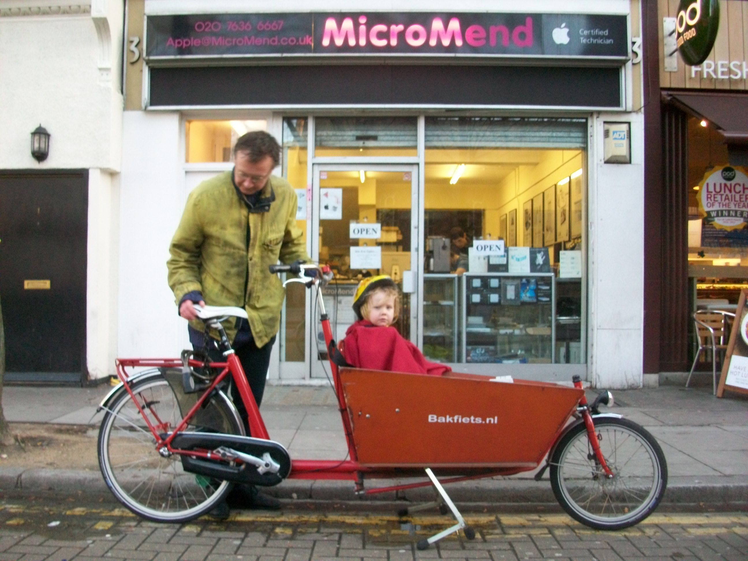 Man with child in cargo bike.