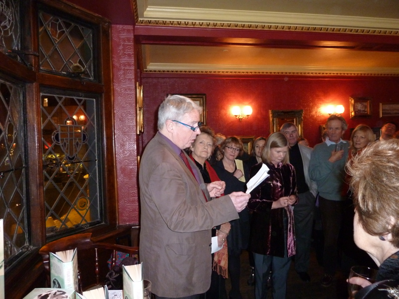 A man reads a poem to people gathered in an upstairs room in a pub.