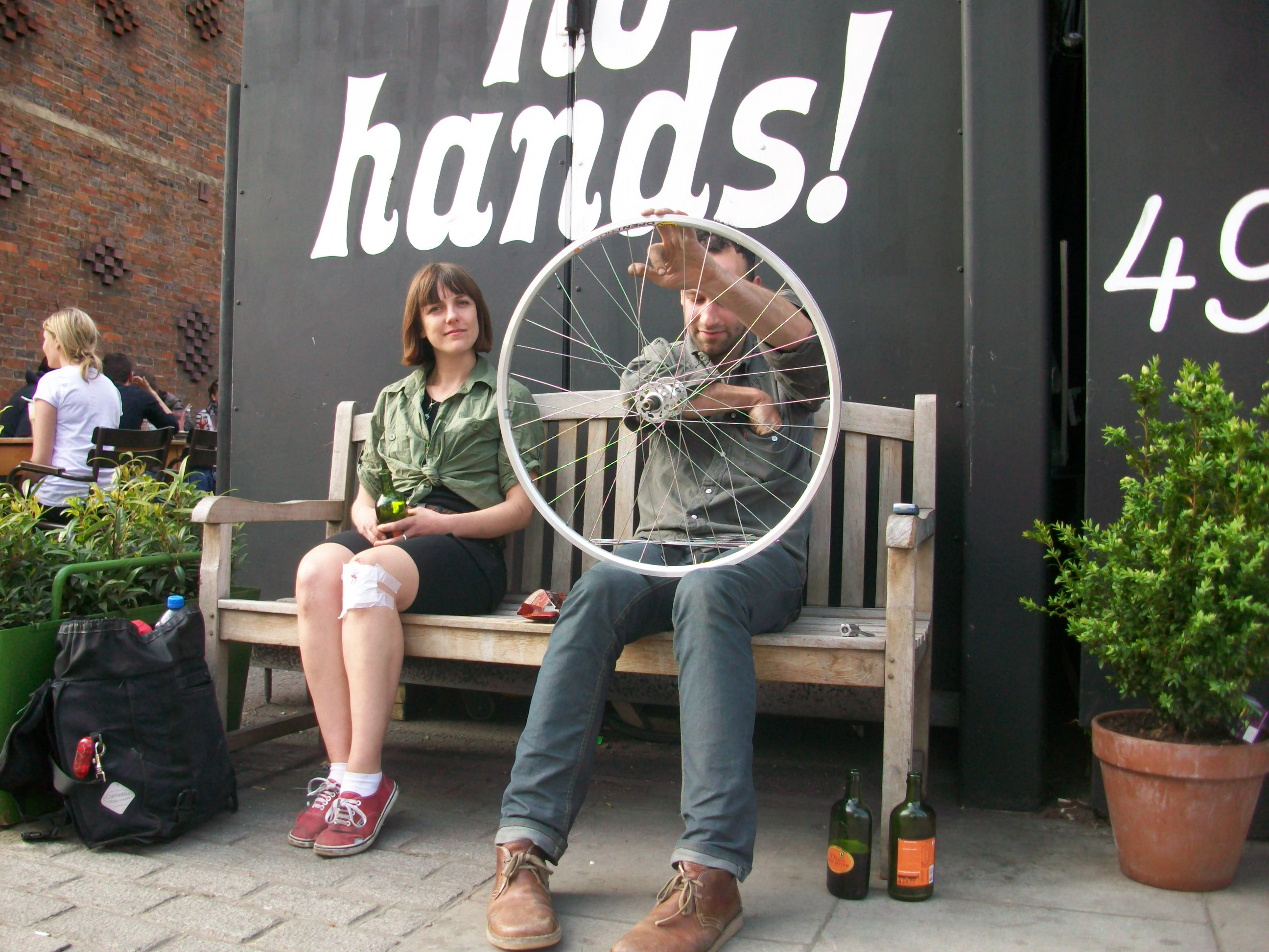 Man and woman sitting on bench outside cycle cafe.