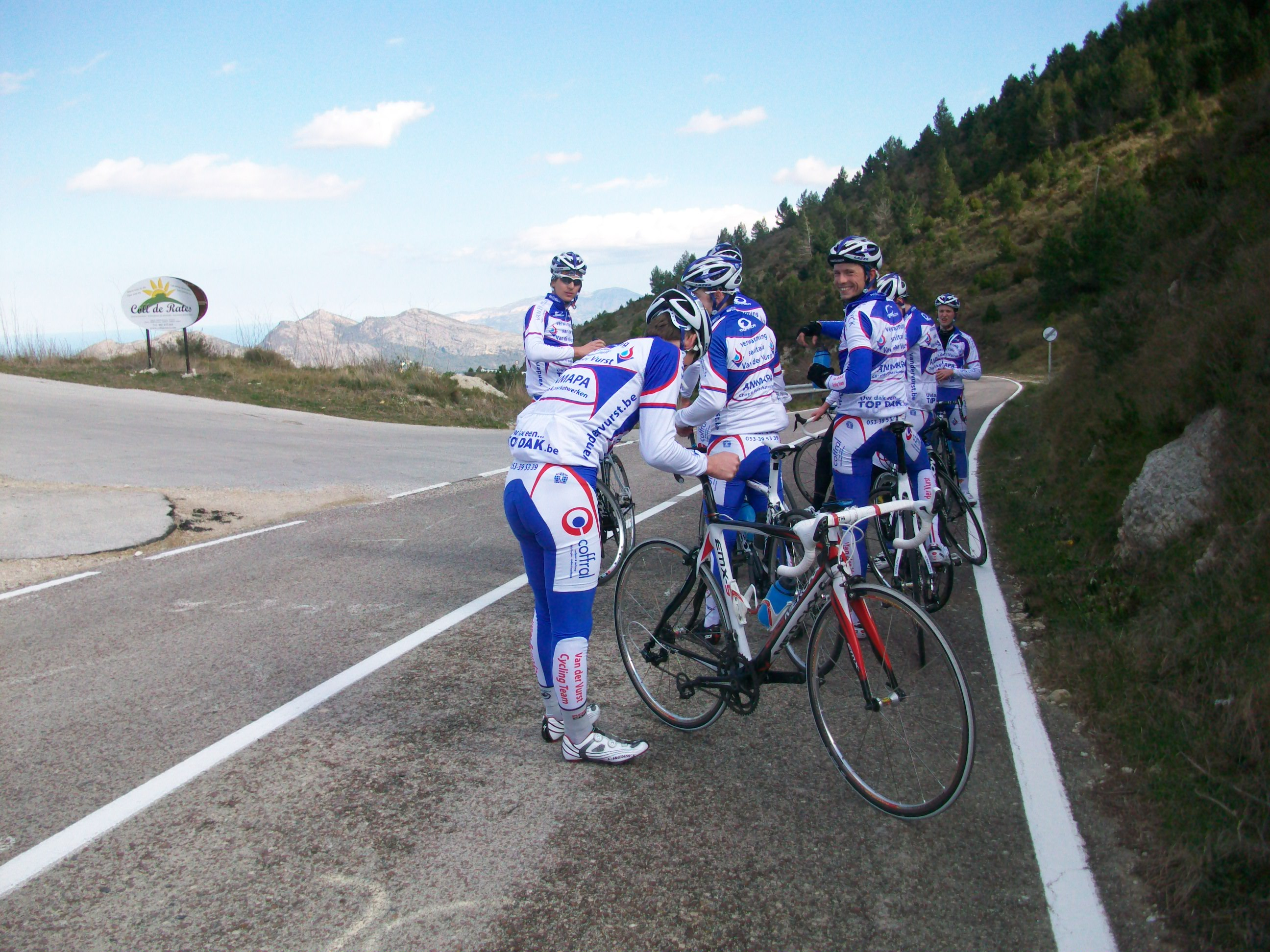 A group of young Belgian cyclists take a break at the top of a mountain pass.