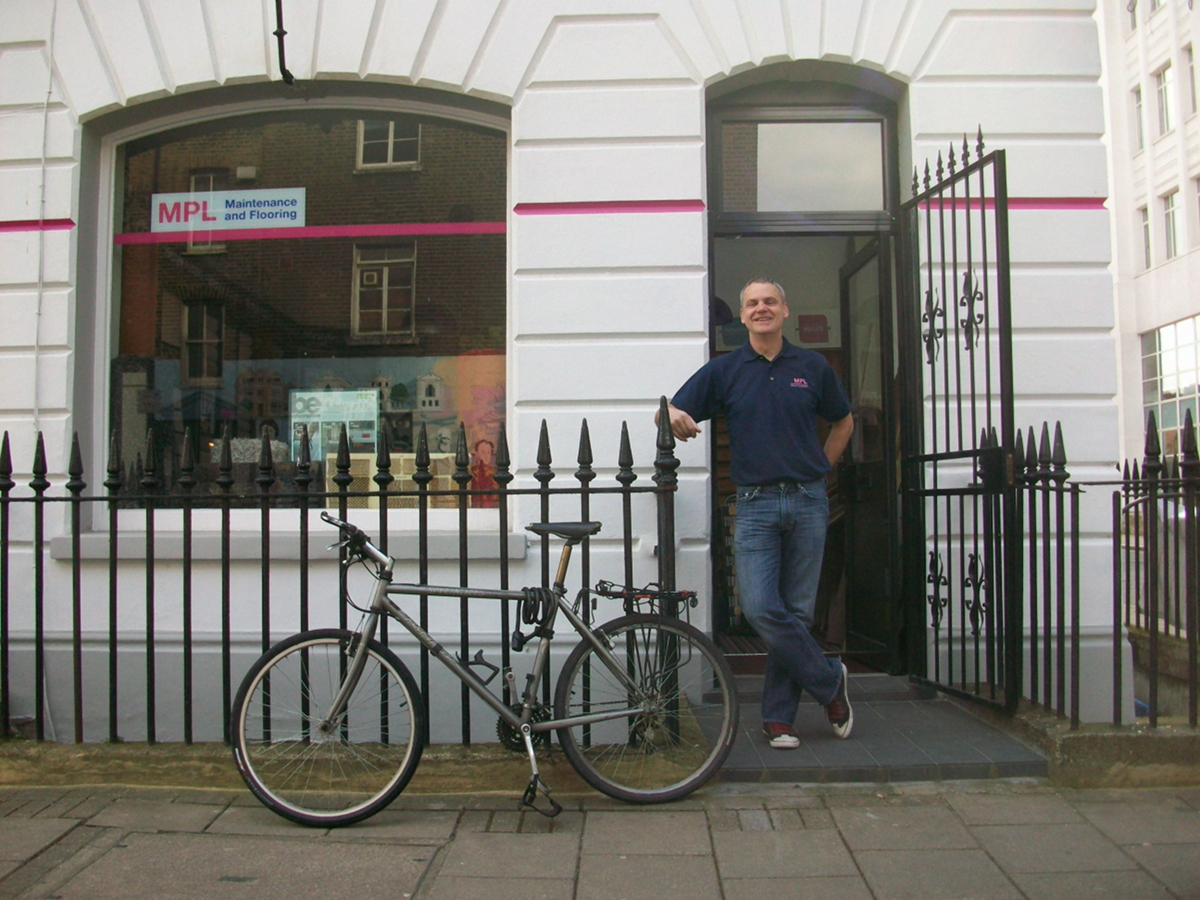 Man with bicycle standing outside office.