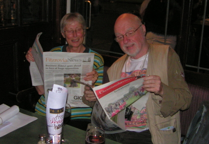 Two people reading newspapers.