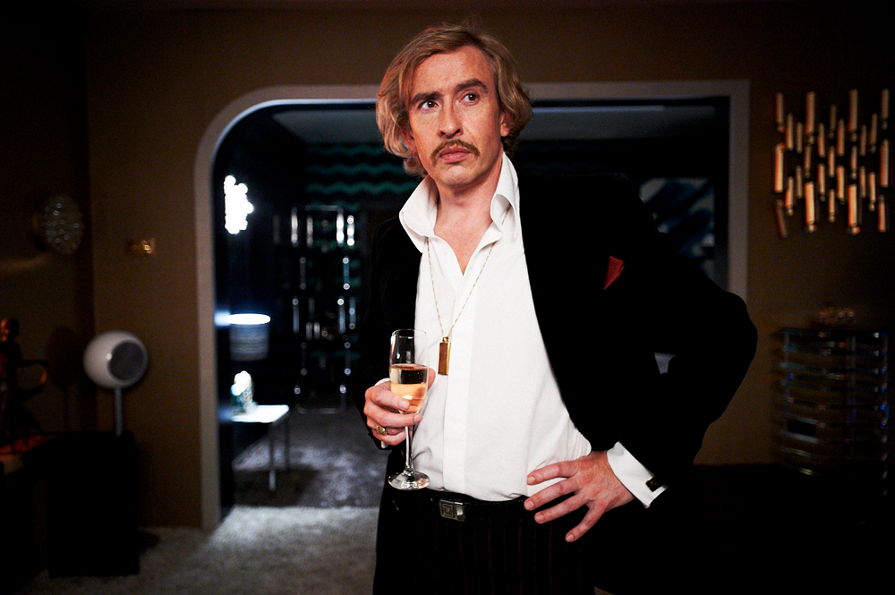 Steve Coogan with wine glass in hand, as Paul Raymond.