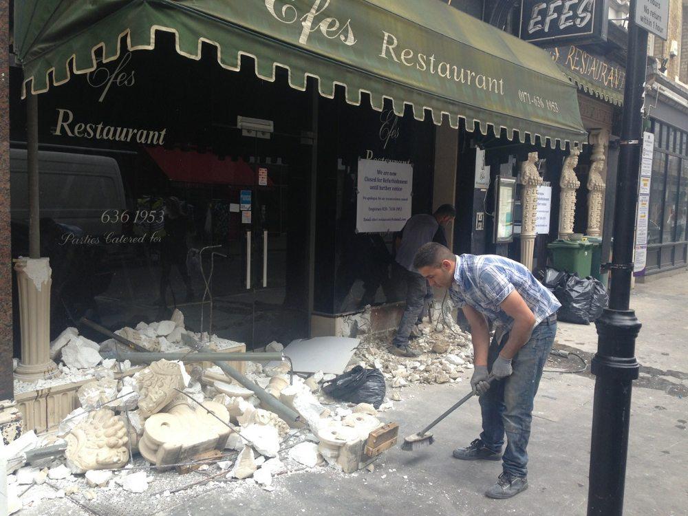Builders demolishing front of restaurant.