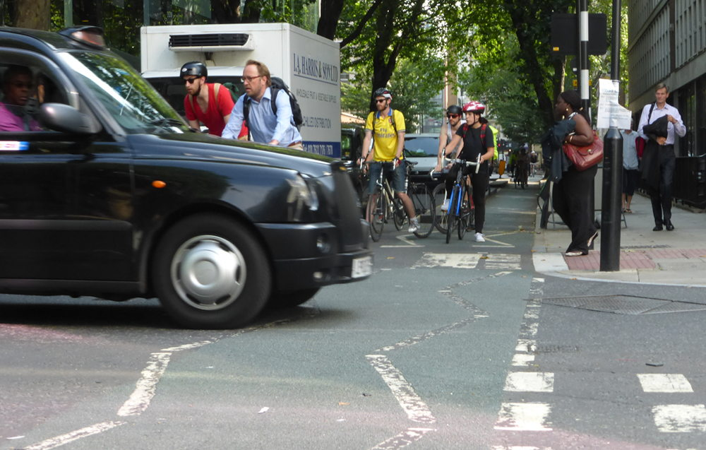 Cycles and motor vehicles at busy junction.