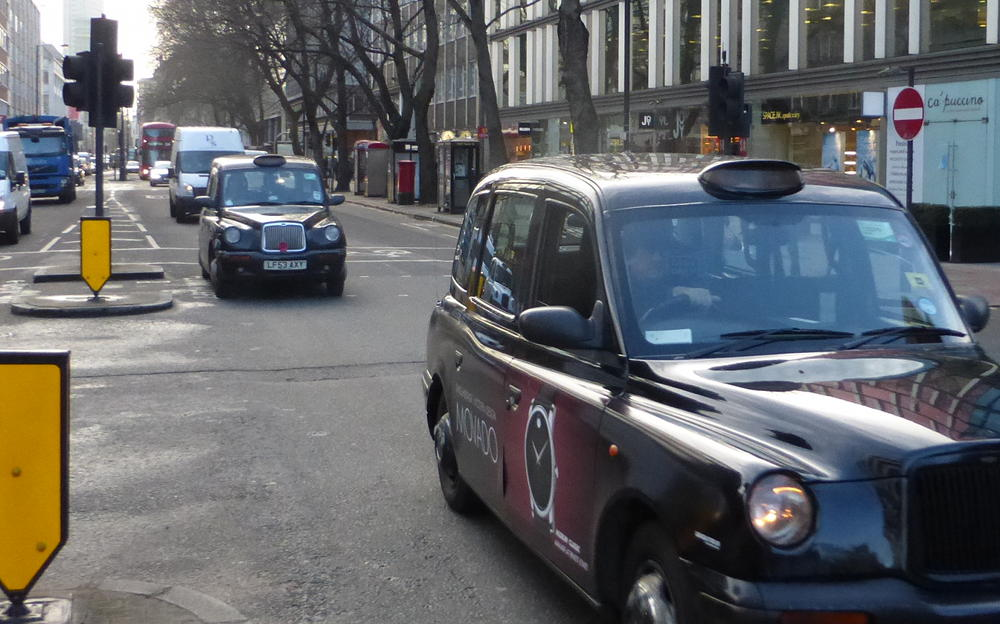 Taxis and delivery vehicles on Tottenham Court Road.
