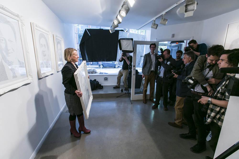 Natalie Bennett stands with framed portrait in gallery.