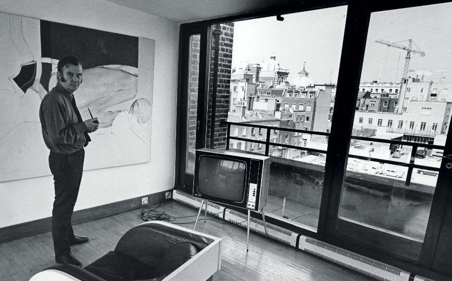 Adrian Heath standing in studio with buildings in background.