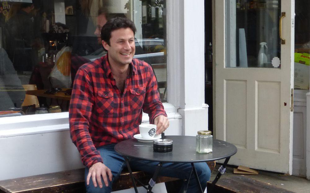 Man sitting outside cafe.