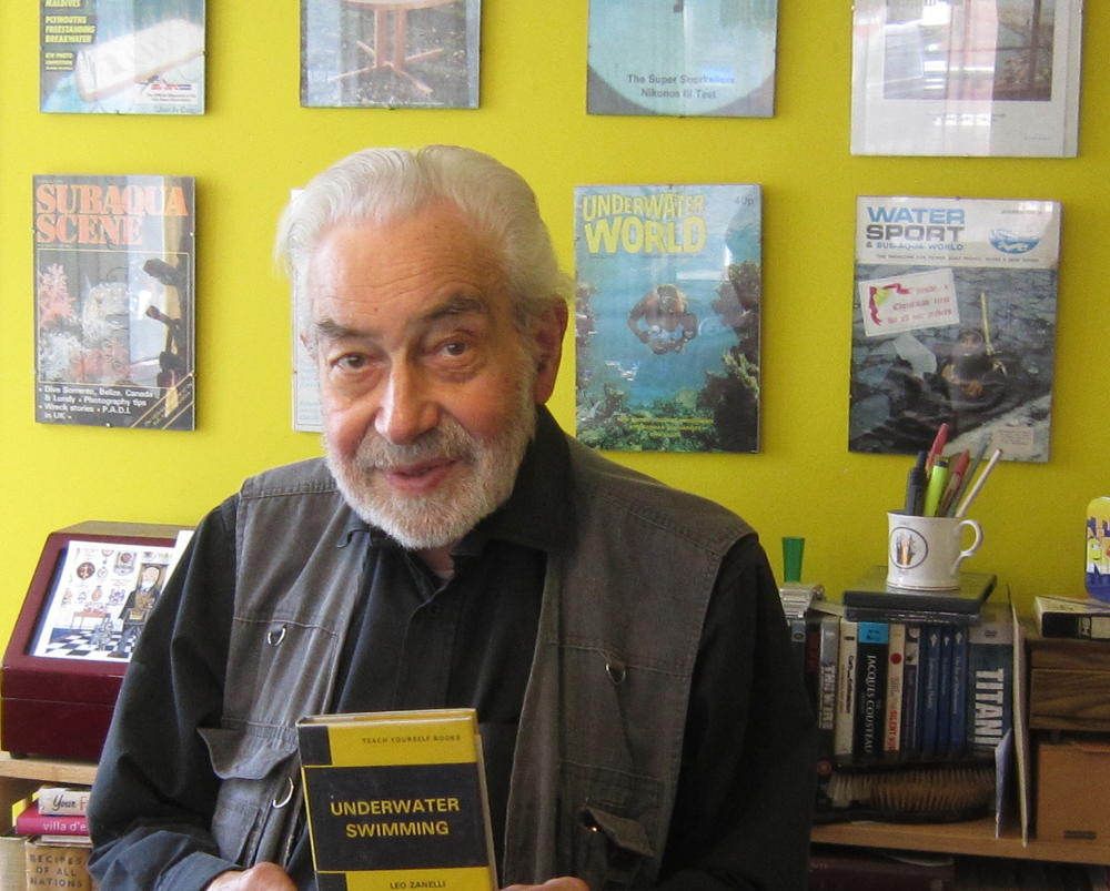 Man holding book in room full of publications.