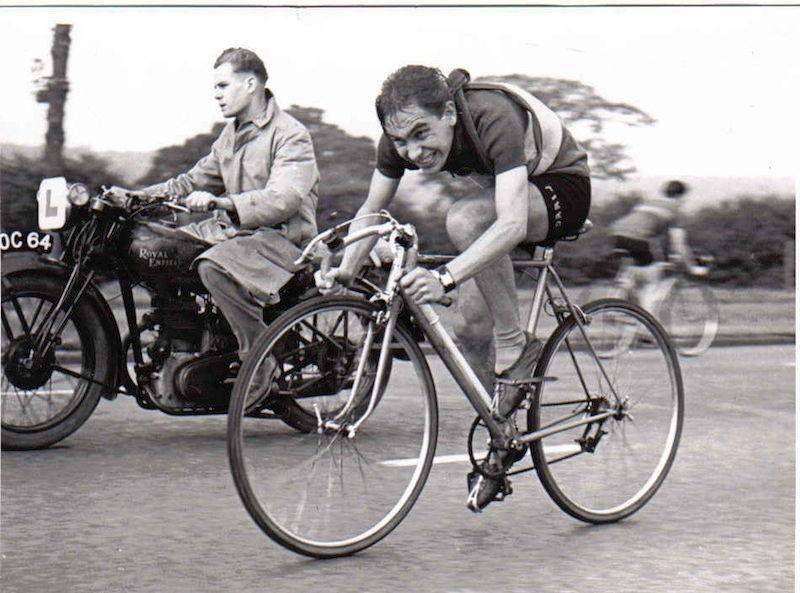 Man cycling alongside motorcycle.