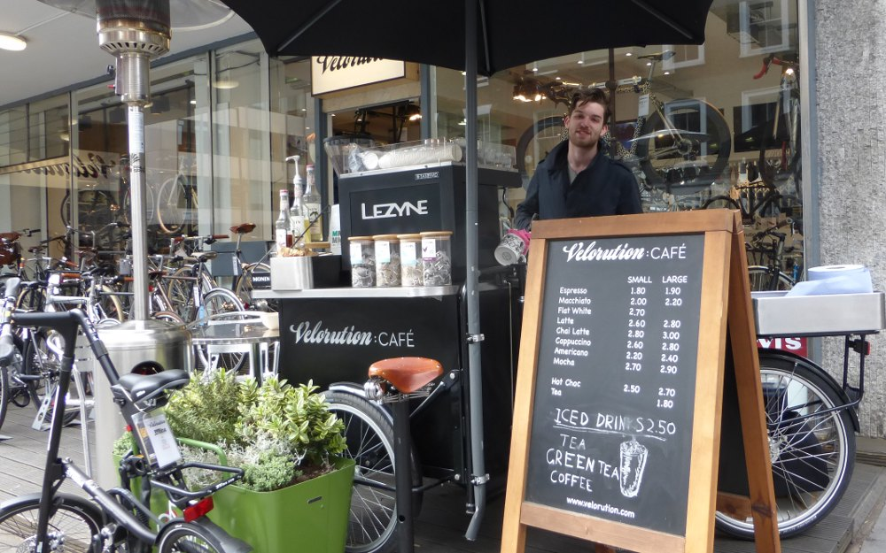 Barista serving coffee outside cycle shop.