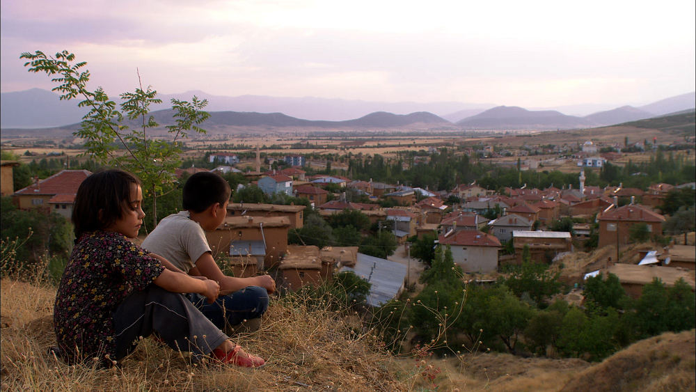 Young boy and girl looking down over a village in Anatolia.