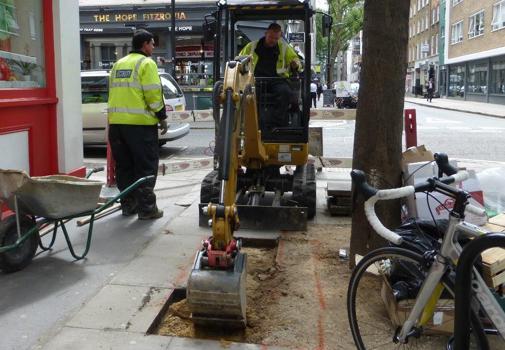 Man operating mechanical digger.