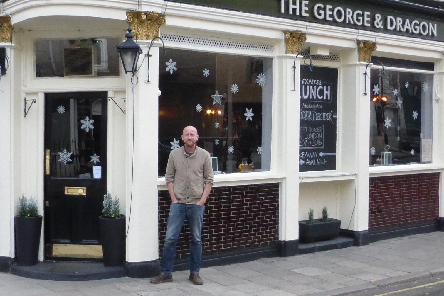 Man standing outside pub.