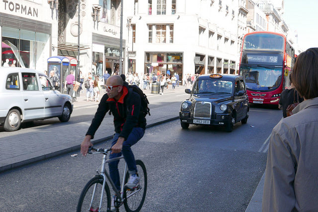 Cyclist, taxi and bus on Oxford Street.