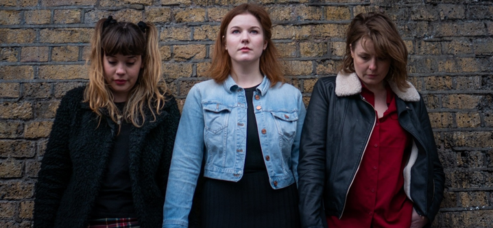 three young women standing against a wall.