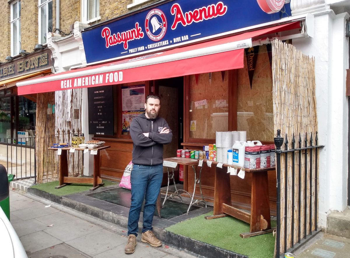 Man standing in front of shop.