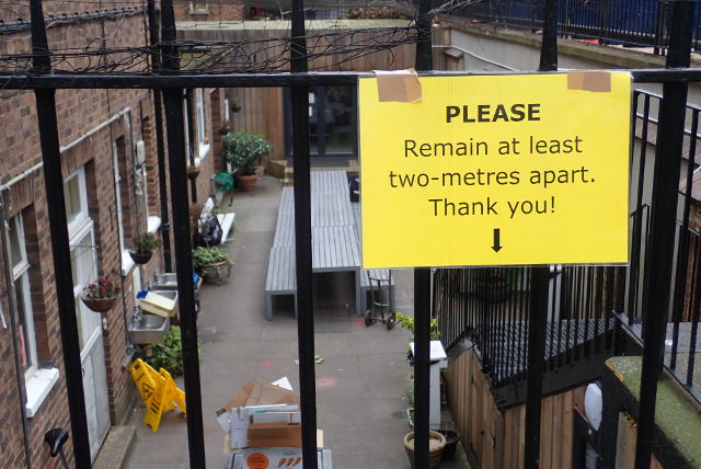 Sign on soup kitchen fence.