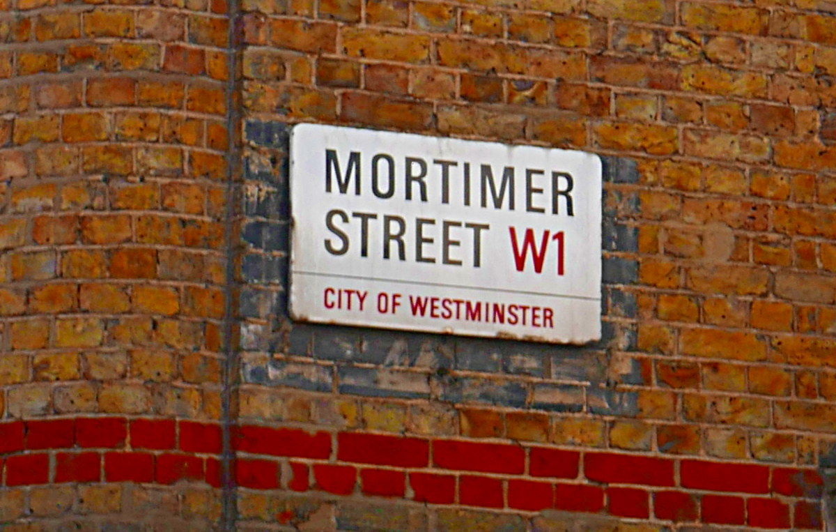 Street sign on wall of building.