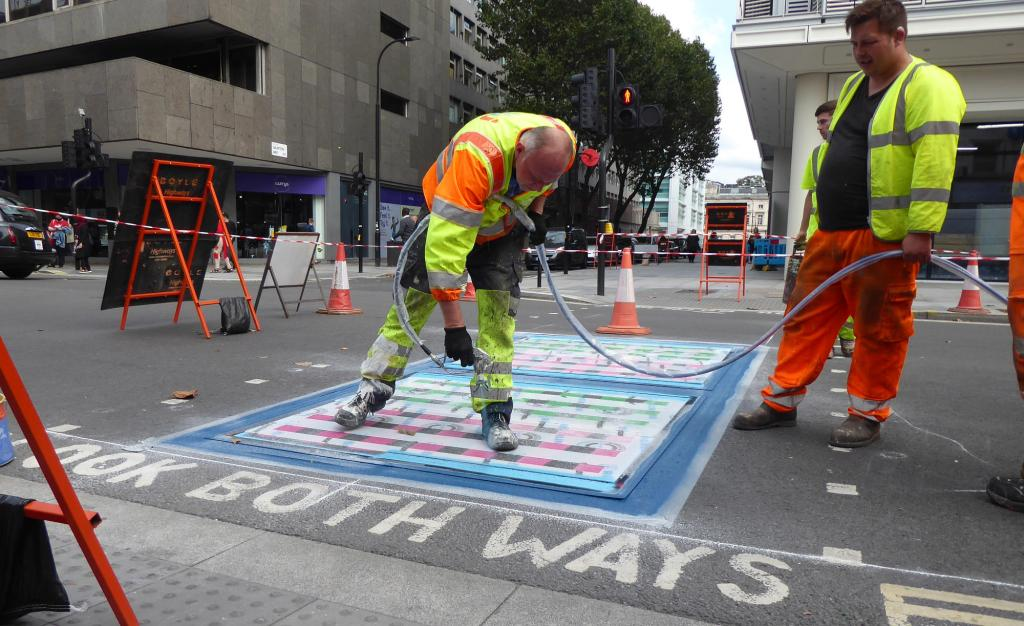 Two workers spray paint to create an artwork on a pedestrian crossing on Tottenham Court Road.